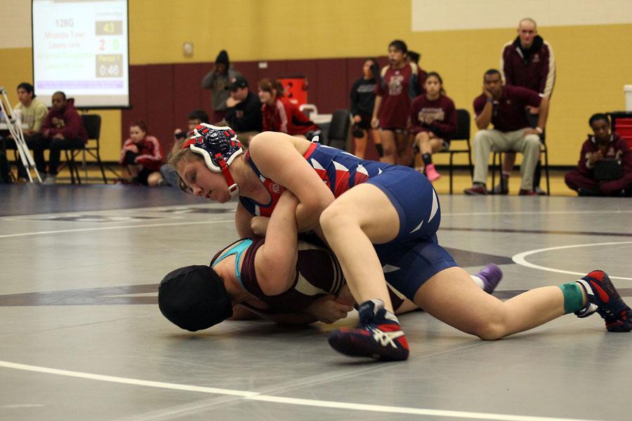Junior Hana Henderson takes a wrestling opponent to the mat on Jan. 18.