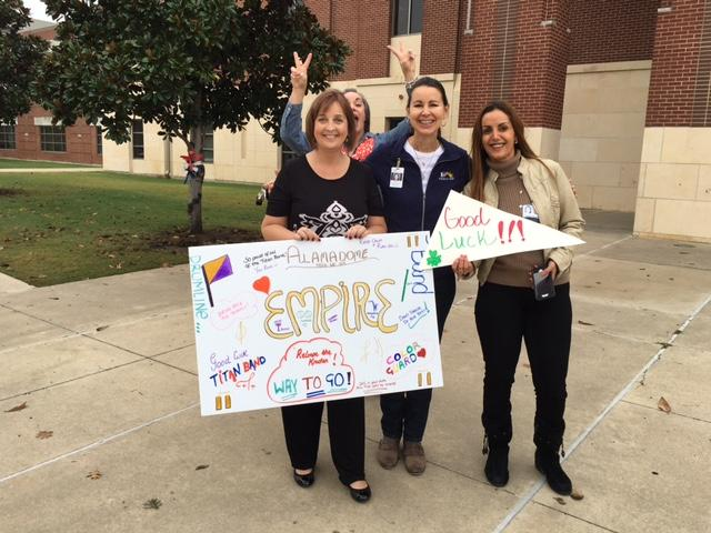 Staff and community members cheer on the band buses as they leave for State!