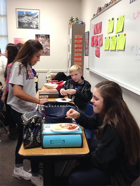 Freshman+Tanya+Giorgetti+talks+with+friends+while+enjoying+Spanish+food+during+a+meeting.