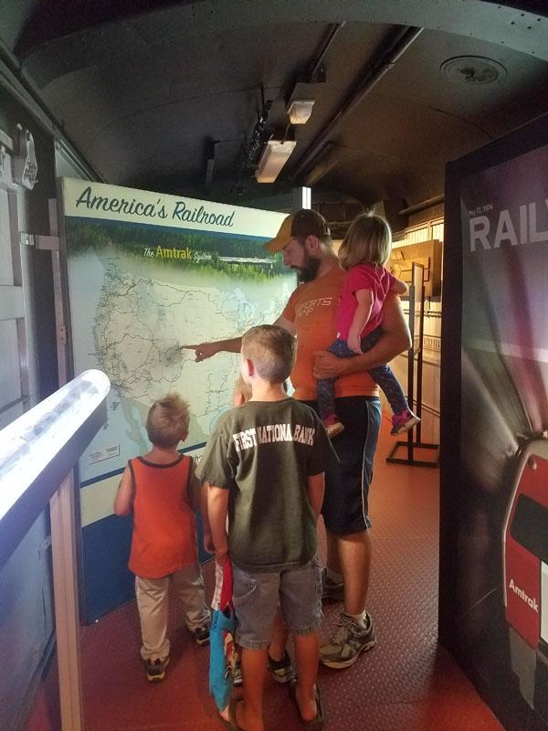 A man and his children explore the train exhibits.
