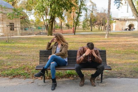 Stressed man and disappointed woman sitting on bench