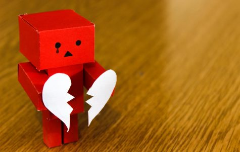 Red toy model with a tear and a white broken heart