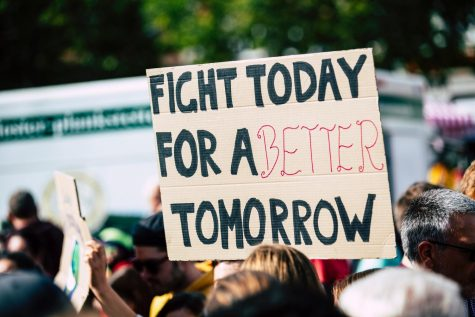 "a person holding up a sign that reads  ""fight today for a better tomorrow""."